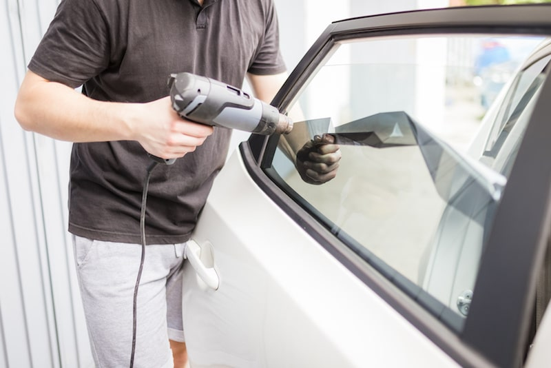 a man using a heat gun on a car window