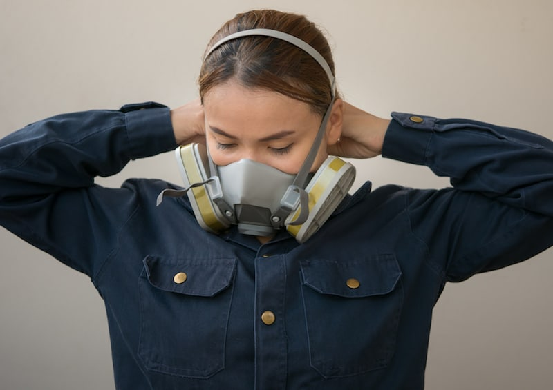 Woman putting on a respirator