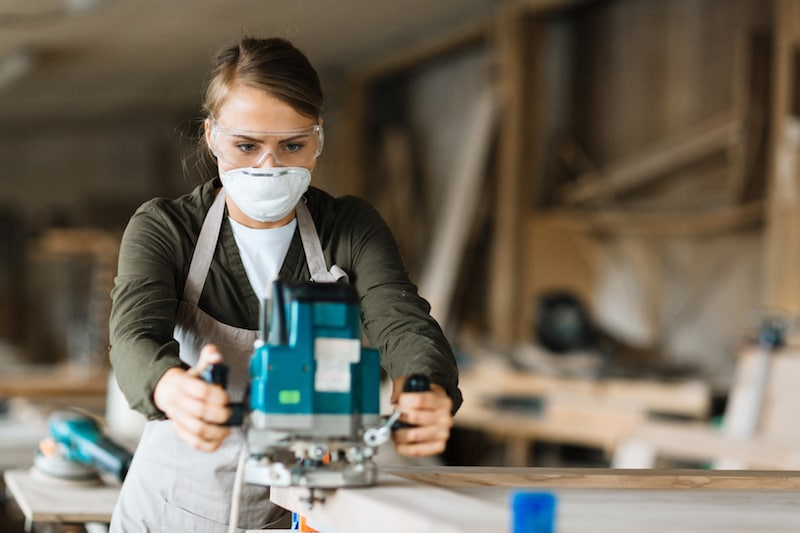 a woman wearing a disposable respirator while using power tools