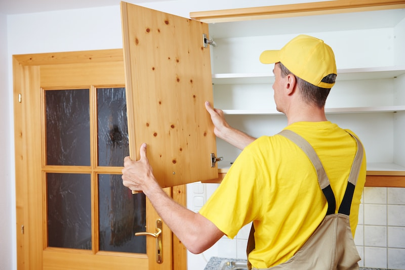 a man in a yellow shirt and hat installing a new wooden door on a cupboard