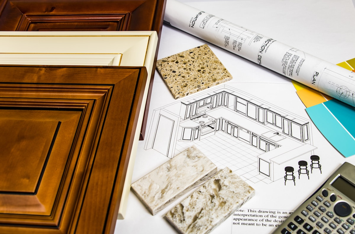 wood samples, granite samples, and a calculator on top of drawn plans for a kitchen