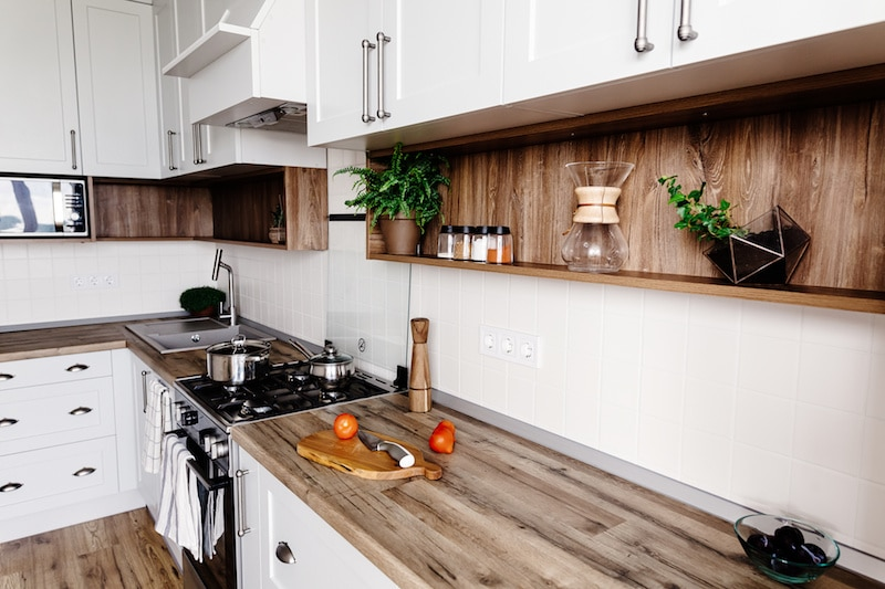 a kitchen with wood countertops and white cupboards