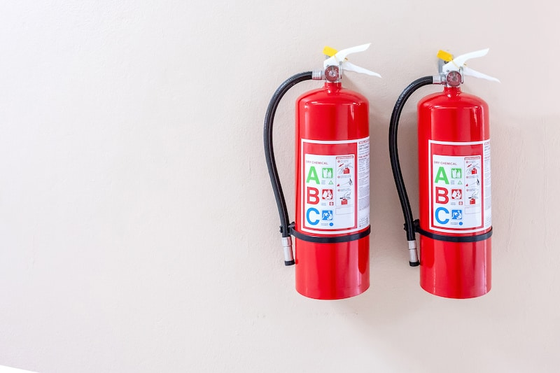 two fire extinguishers mounted on a wall that are good for class a b and c fires