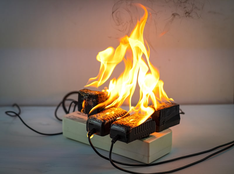 fire breaking out on an electrical strip with several things plugged into it