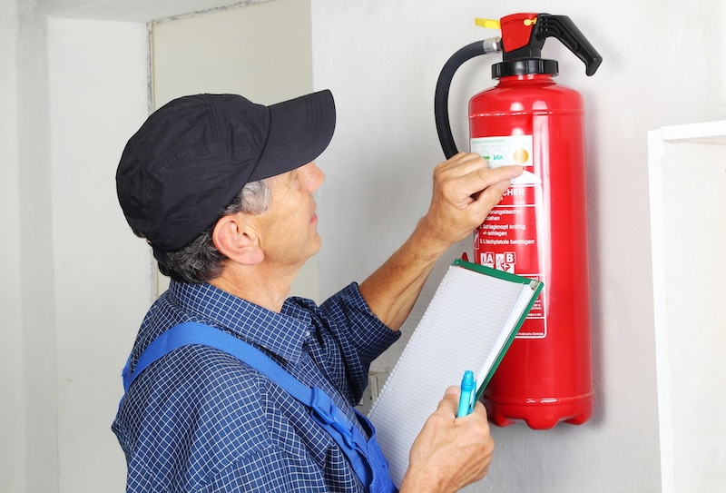 a man in blue overalls inspecting a fire extinguisher and holding a pad of paper