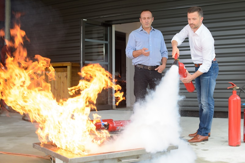 a man practicing using a fire extinguisher on a controlled fire while another man teaches him